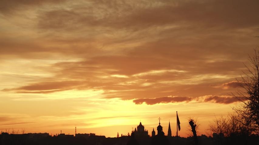 Orange fiery sunset sunrise cloudy sky over city horizon. Skyline buildings silhouettes. Enjoying nature beauty. Evening time. Traveling. Natural landmark. Urban lifestyle. Amazing setting sun down. | Shutterstock HD Video #1042803289