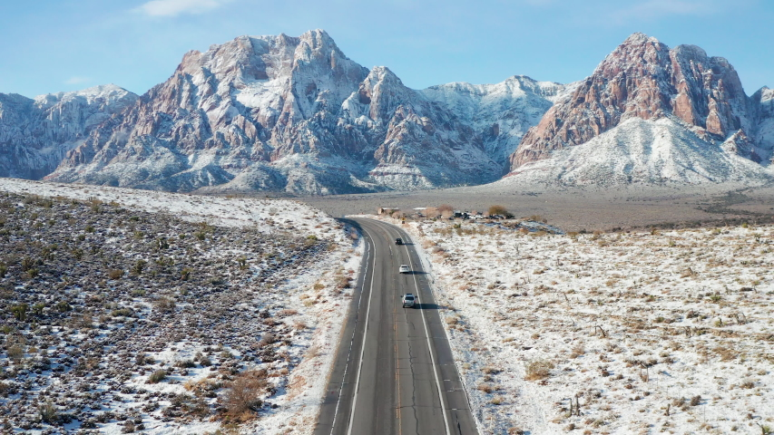 Aerial pullback shot of cars, snow desert mountain landscape in Red Rock Canyon | Shutterstock HD Video #1043679799