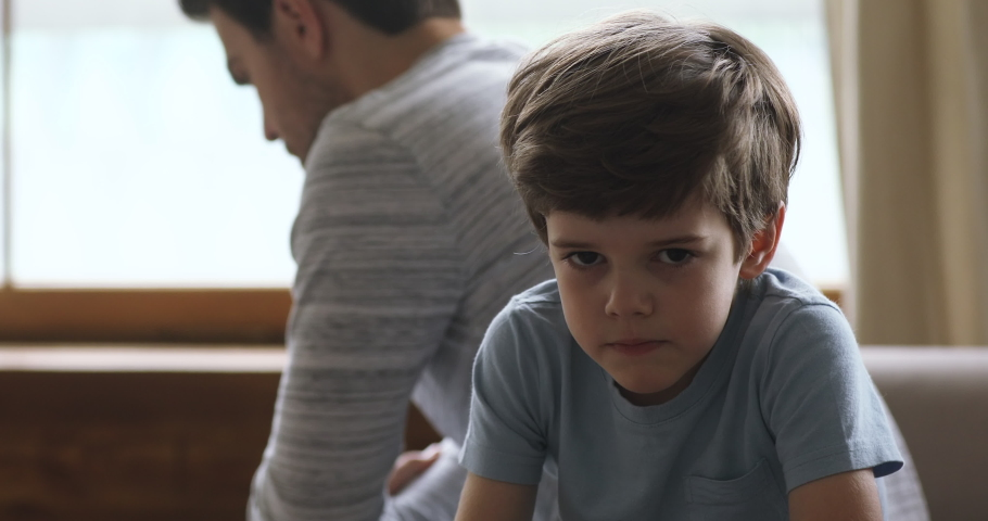 Sad preschool kid son sulking thinking of family conflicts sit turn back to unhappy dad, punished scolded little upset guilty child boy stubborn behavior in bad relationship with father concept | Shutterstock HD Video #1044100459