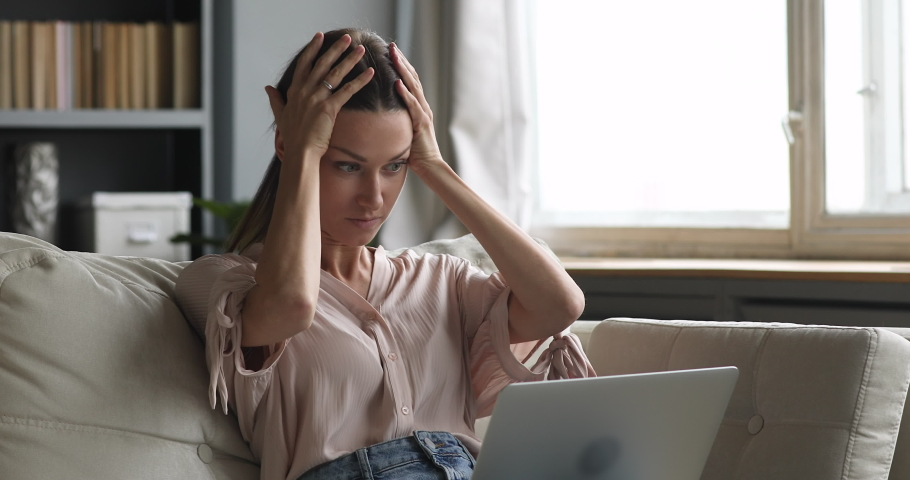 Angry upset young woman user customer using laptop feel frustrated mad about computer problem, stressed about mistake software error, worried reading bad news in social media sit on couch at home | Shutterstock HD Video #1044454849