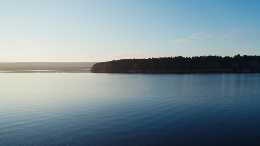 Flying over blue water in the evening. Beautiful calm river on trees background in nature at sunset. Motion camera forward. | Shutterstock HD Video #1044901669