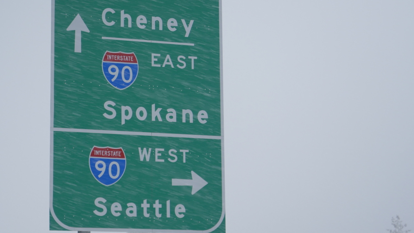 CLOSE UP: Traffic sign weathers a severe blizzard engulfing the state of Washington. Green highway traffic sign directs traffic around the state of Washington during a snowstorm. Extreme weather. | Shutterstock HD Video #1044956449