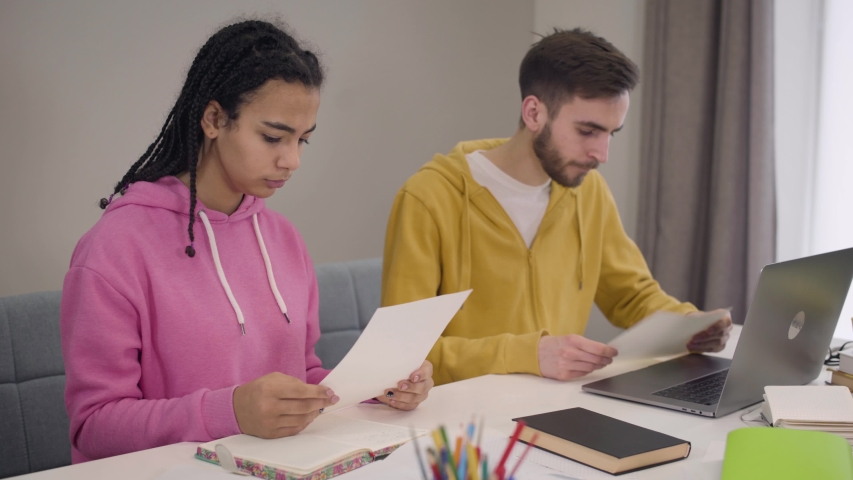 Young university students sitting at the table with papers and talking to each other. Serious smart African American girl and Caucasian boy studying together. Lifestyle, intelligence, education. | Shutterstock HD Video #1045058359