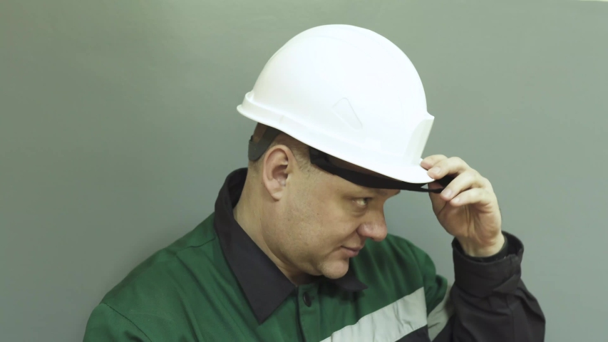 The face of a man in a work uniform of an engineer at work. The engineer speaks on the radio, puts on a helmet, glasses, and turns on a flashlight.  | Shutterstock HD Video #1045091569