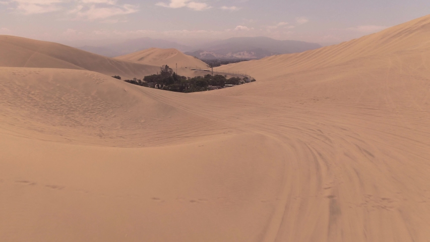 Sandy desert oasis lake. DRONE. Water in middle of hot sand desert. Romantic, holiday, couple, honeymoon, scenic shot, with sand and footprints. Tourism shot in Huacachina, Peru. Epic, dramatic shot. | Shutterstock HD Video #1045192789