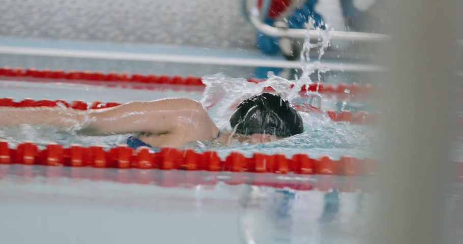 Young professional female swimmer swims in the pool, woman swimming and training in the water. | Shutterstock HD Video #1045215679