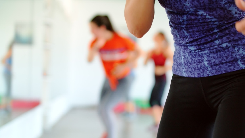 Close up shot of dance fitness zumba class group of beautiful women dancing enjoying workout practicing choreography moves with instructor in fitness studio, 4k slow motion | Shutterstock HD Video #1045226509
