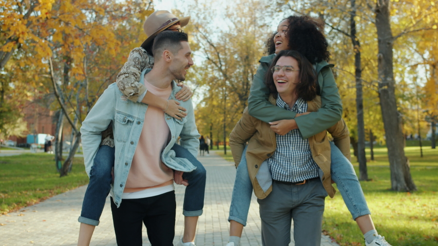 Portrait of happy guys friends giving piggyback ride to girls laughing in city park, cheerful young women are doing high-five. Friendship and fun concept. | Shutterstock HD Video #1045402189