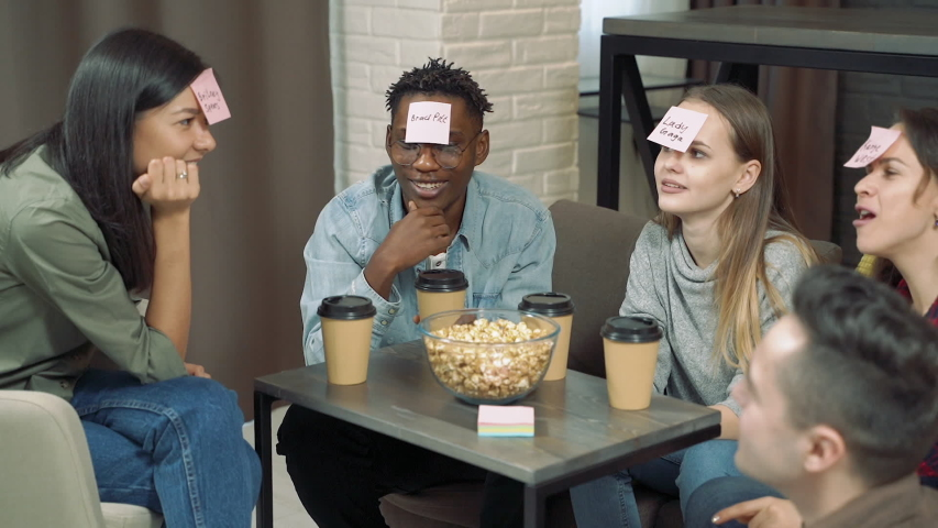 """Diverse group of friends playing """"Who am I"""" game with sticky papers attached to foreheads. Friendship, leisure and entertainment concept 