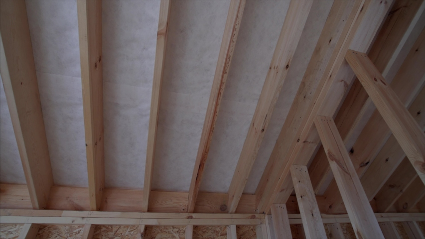 Panoramic view of ceiling of unfinished wooden frame house: planks, beams and empty doorway. Interior of a cottage under construction | Shutterstock HD Video #1045438009
