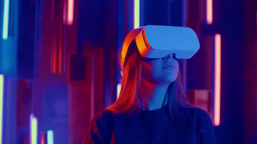 Faceless woman wearing VR headset in dark space with neon light lamps, user turning head side to side looking virtual reality, shoting through colored flares and bokeh on foreground.   Shutterstock HD Video #1045442539