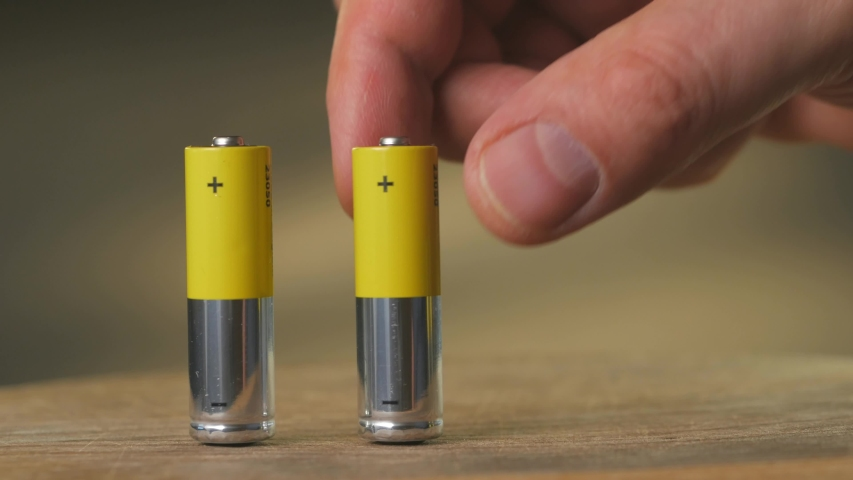 Closeup of the fingers of a man put on a wooden table with four AA batteries | Shutterstock HD Video #1045451089