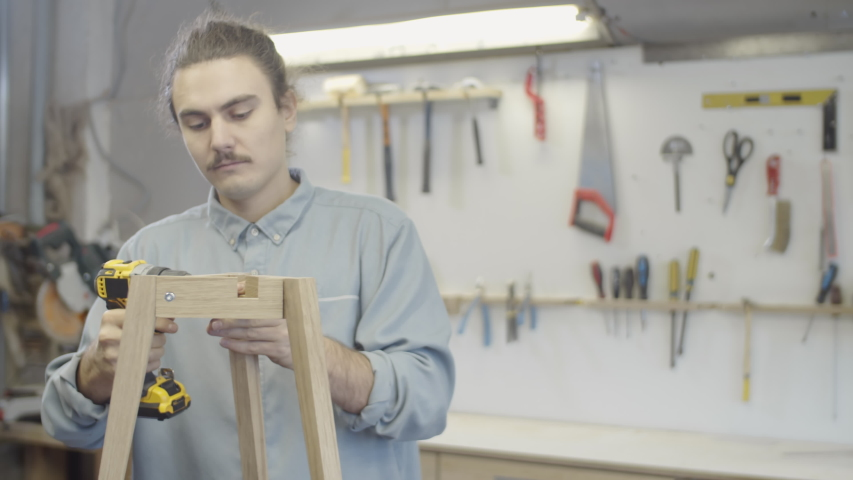 Waist-up arc shot of young Caucasian craftsman assembling custom handmade wooden table base with three legs at carpentry workshop, using power drill tool to tighten screws | Shutterstock HD Video #1045464259