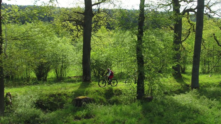 Young couple mountain biking along a beautiful track in springtime | Shutterstock HD Video #1046023579