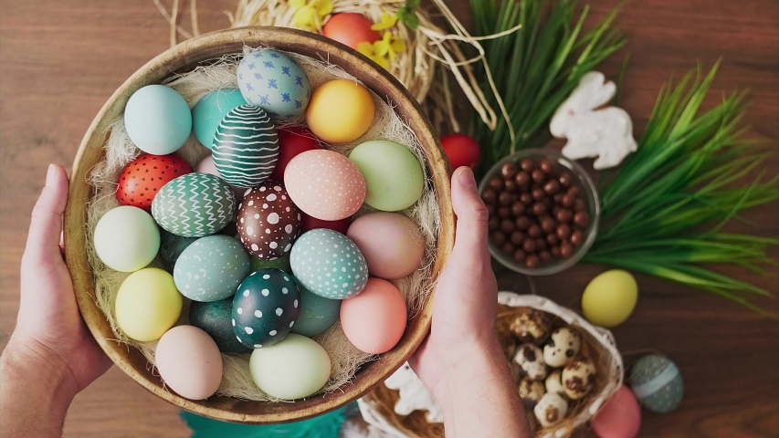 Hands holding basket full of colorful Easter eggs in front of decoration on wooden table. Easter holiday decorations, Easter concept background.  | Shutterstock HD Video #1046134489