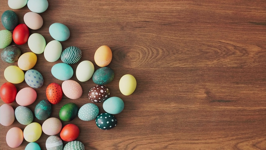 Hands Taking colorful Easter eggs of wooden table. Easter holiday decorations, Easter concept background.  | Shutterstock HD Video #1046134549