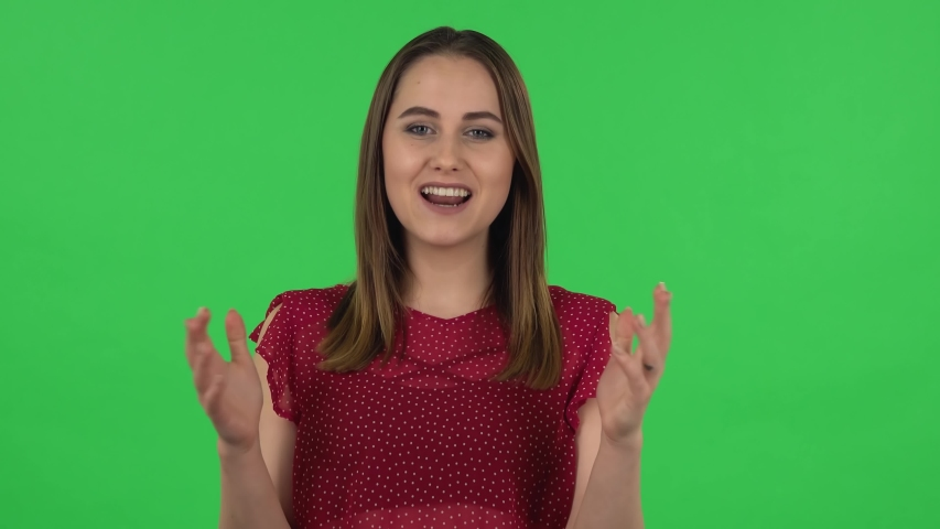 Portrait of tender girl in red dress is reporting and telling a lot of interesting information. Green screen | Shutterstock HD Video #1046737219