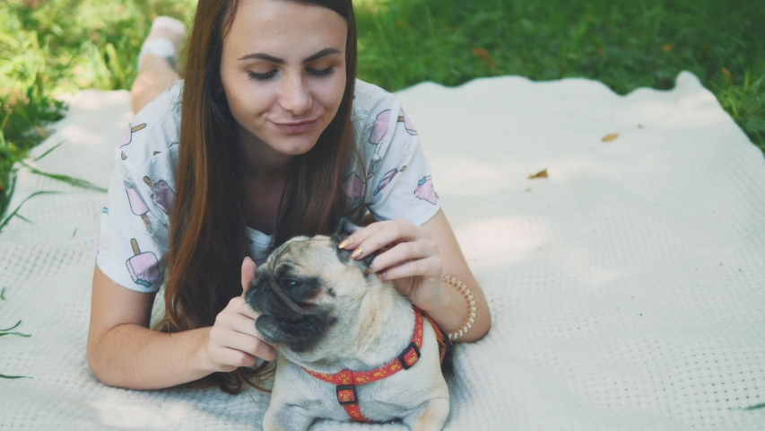 Smiling lady is taking free time with her dog. Woman relaxing in the nature with her little pug dog. Close up. Copy space. 4K. | Shutterstock HD Video #1046771089