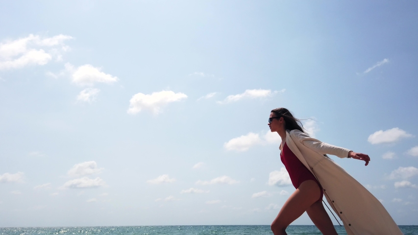 Young lady in red swim suit, long white dress and sun glasses runs on beach on background of blue sky with clouds. View from below. Positive. Dress fluttering on wind. Honeymoon. Super slow motion.    Shutterstock HD Video #1046805619