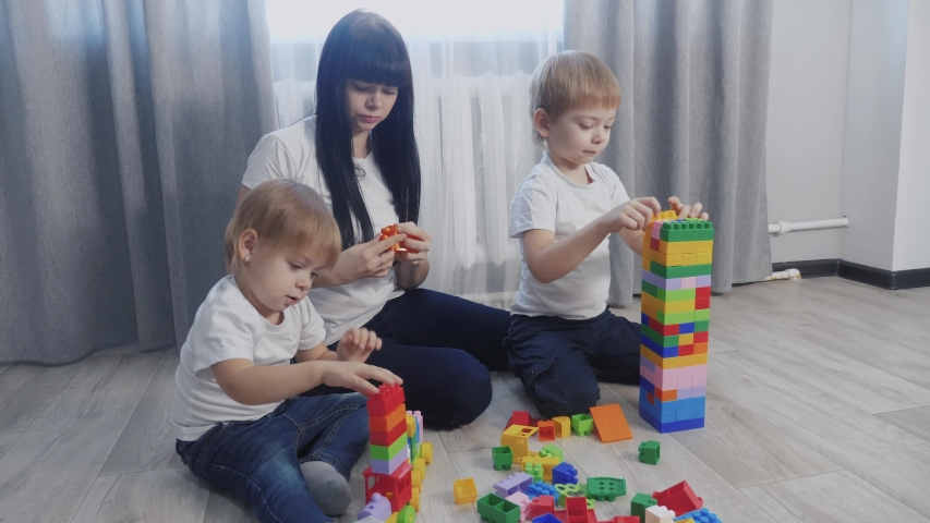 Childhood happy family mom and children are playing concept little girl and boy brother and sister collects constructor teamwork. child lifestyle plays toys sitting on floor. children play in a team | Shutterstock HD Video #1046814889