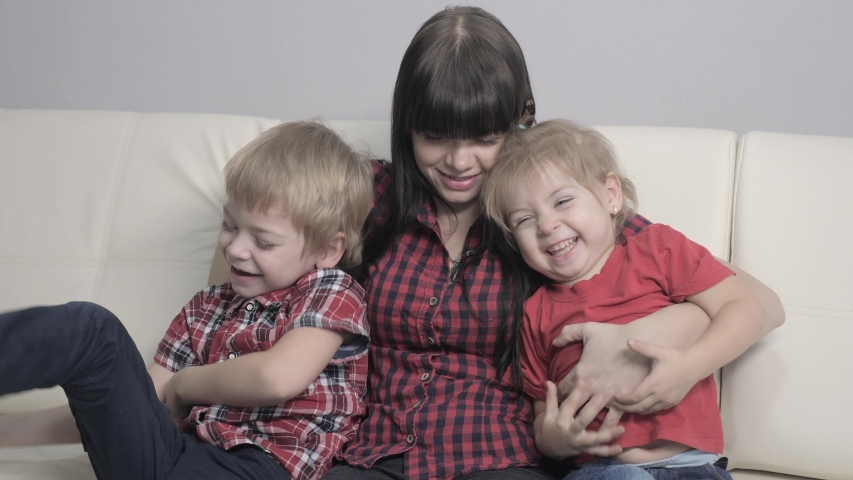 Happy family little boy and girl laughs from lifestyle tickling mother. woman playing with son and daughter a happy family laughing indoors | Shutterstock HD Video #1046890879