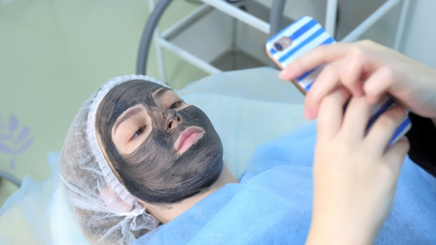 Patient woman is typing message on smartphone on carbon peeling procedure in beauty clinic with beautician. Portrait of woman with carbon nanogel on face lying on couch in cosmetology salon. | Shutterstock HD Video #1046914129
