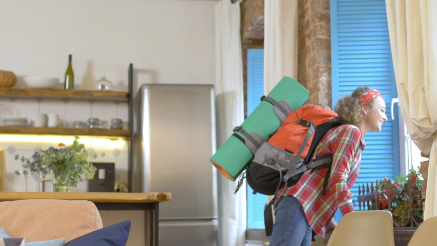 Happy smiling woman tourist with backpack enjoying rented modern loft acommodations. Traveler abroad renting apartment. Cheerful girl backpacker in rented home. | Shutterstock HD Video #1046956399