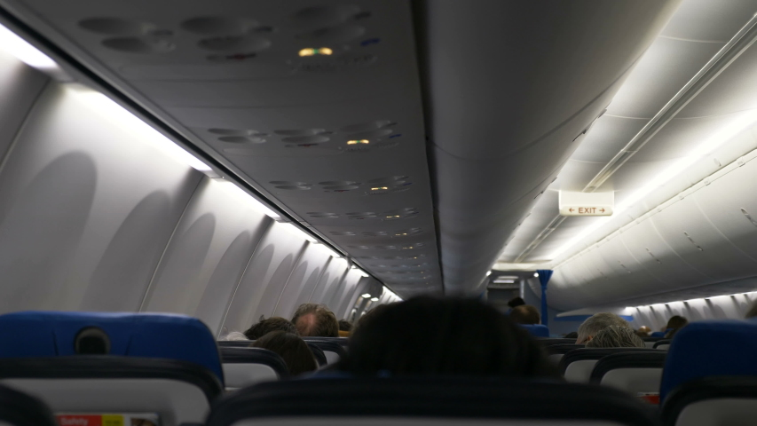 Relaxed passengers sit in several rows according to boarding passes traveling in comfortable plane backside view | Shutterstock HD Video #1046964589