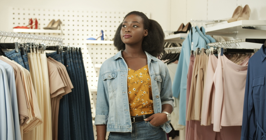 Portrait shop of cheerful young African American pretty woman smiling to camera in clothing store. Beautiful girl laughing at shopping in shop of fancy clothes. Female fashion shopaholic. | Shutterstock HD Video #1046966179