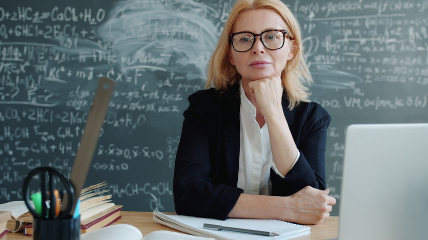 Serious adult woman is sitting at desk in university classroom looking at camera wearing suit and glasses. Profession, lifestyle and education concept. | Shutterstock HD Video #1046967079