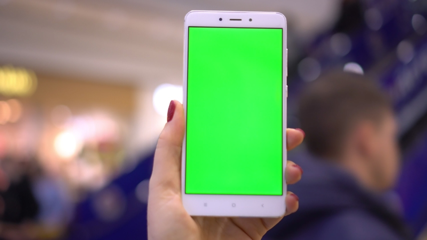 Female hand holding smartphone with green screen. Girl using mobile phone while walking in the shopping center. Back view shot. Chroma key, close up woman hand holding phone with vertical green screen | Shutterstock HD Video #1047009529