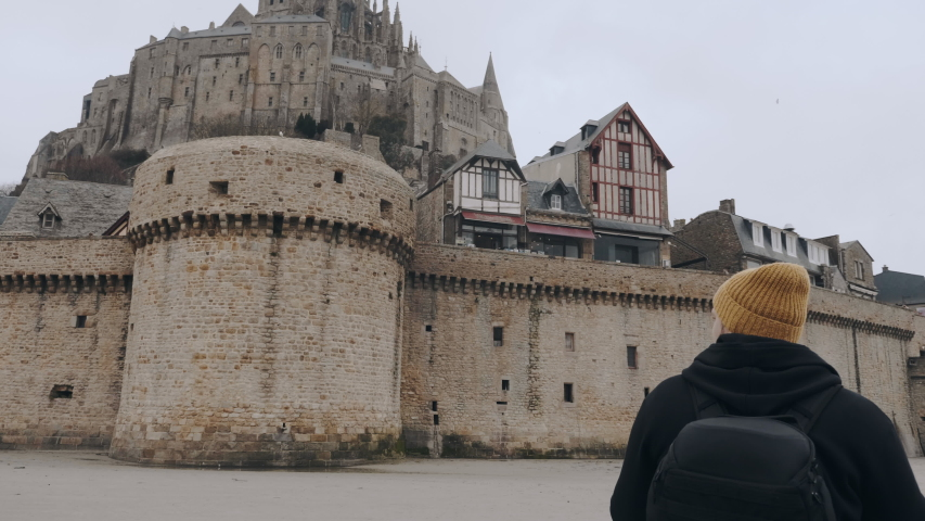 Camera moves around happy excited tourist man with backpack stunned by epic Mont Saint Michel castle fort slow motion. | Shutterstock HD Video #1047096919