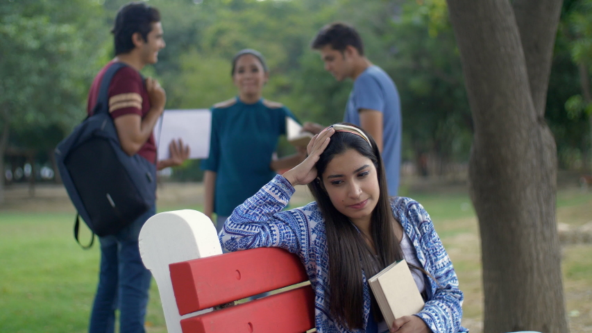 A young college student is very sad and depressed after failing the examination. Stressed and unhappy Indian girl is disappointed by her exam results while her classmates are celebrating success in... | Shutterstock HD Video #1047111799