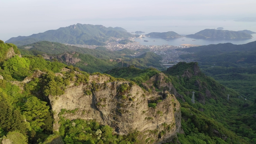 Aerial view from above Takatori Viewpoint overlooking rugged cliffs and green forests of Kankakei Gorge on Shodoshima Island with a village on the coastline & islets in Seto Inland Sea in Kagawa Japan   Shutterstock HD Video #1047113689