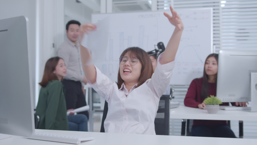 Excited Asian Businesswoman Sitting at her office desk arms raised celebration of successful project, job promotion. Her Colleagues are Clapping and Happy. Successful Businesswoman Concept. | Shutterstock HD Video #1047146509