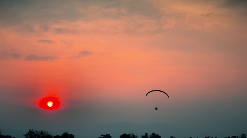Extreme sport paramotor Flying at Sunset and Beautiful Sky | Shutterstock HD Video #1047178339
