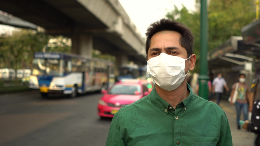 A man wearing mask protective for spreading of disease virus Covid-19 and air smog pollution with PM 2.5 on street at chatuchak district in  Bangkok city, Thailand. | Shutterstock HD Video #1047319189
