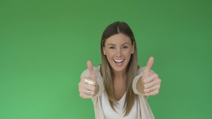 Portrait of cheerful woman showing thumbs up on green background, isolated | Shutterstock HD Video #1047332689