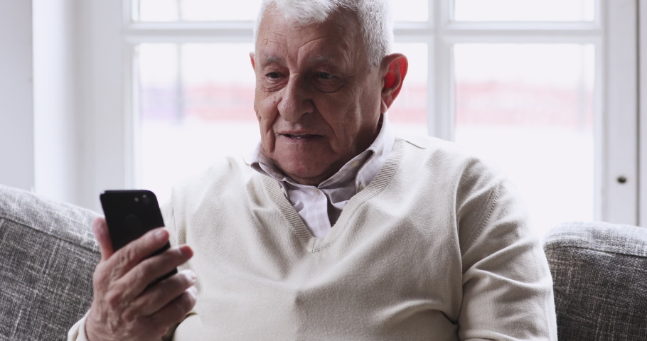 Happy senior elderly 70s man user holding smart phone watching mobile video calling online looking at screen relaxing on couch at home, older grandparent learn using modern technology gadget concept. | Shutterstock HD Video #1047425119