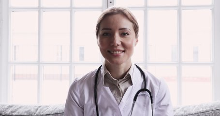 Smiling young female doctor wear white uniform stethoscope consulting online patient via video call looking at camera speaking cam do distance video chat, telemedicine and e-health concept, webcam