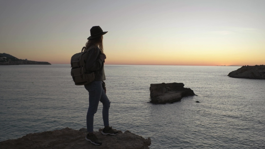 Female traveller standing on viewpoint at sunset, Ibiza | Shutterstock HD Video #1048611619