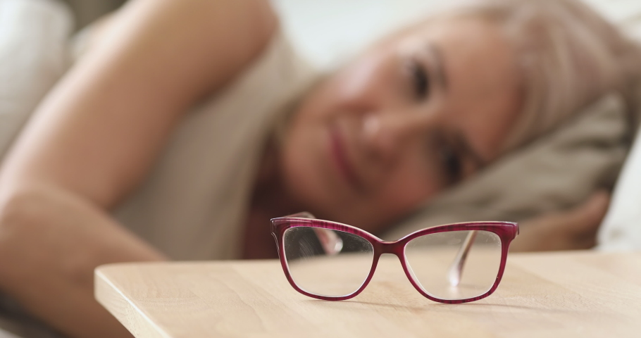 Focus on eyeglasses lying on bedside table. Older mature woman waking up in morning, taking optical glasses from nightstand, close up. Elderly people bad vision, blurred eyesight problem concept. | Shutterstock HD Video #1048820599