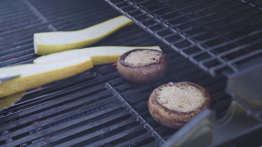 Grilling New York steak with a slice of butter and rosemary on an outdoor gas grill. | Shutterstock HD Video #1048864189