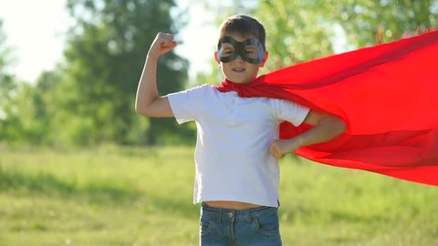 Superhero kid outdoors. Little Boy wearing Super hero costume showing muscles and Running In Summer Park. Full HD 1080p