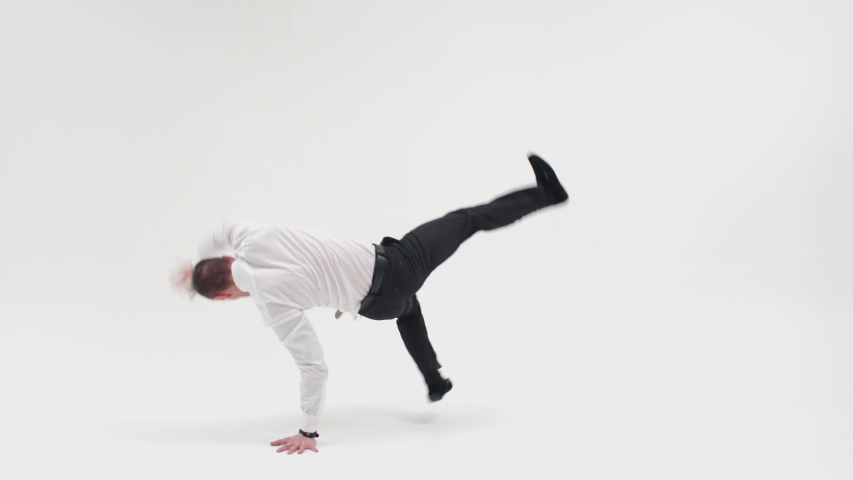 A man in office clothes is dancing a break dance. An office worker dances a break dance and makes a twist movement | Shutterstock HD Video #1049067049