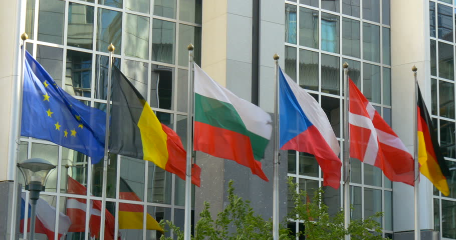 BRUSSELS BELGIUM EUROPE 14 SEP 2014: Close up pan tilt right up motion video of all euro countries national flags waving in front of European Union (EU) Parliament politics institution office building