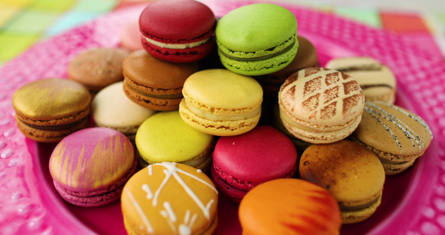 Many french macarons selection of colorful pastries on pink dessert plate. Retro vintage home kitchen background. Assortment of fancy pastry macaroons tasting. | Shutterstock HD Video #1049488249