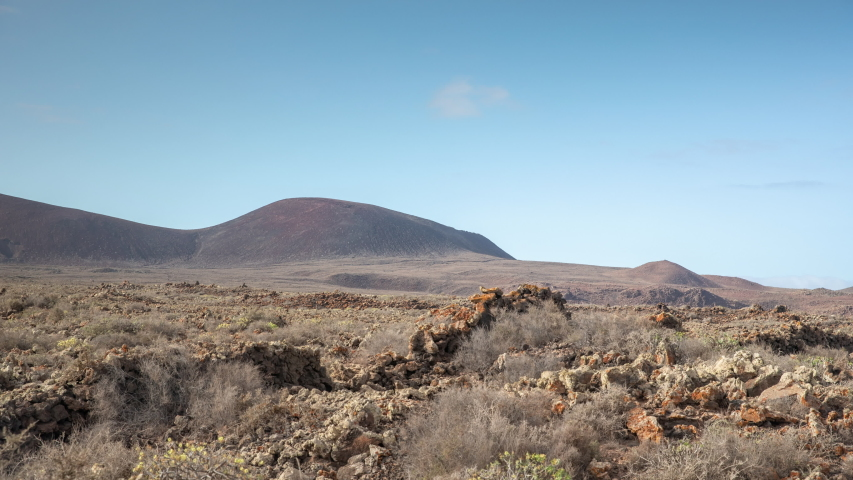 Zooming out timelapse of clouds passing over wild arid landscape of Volcano de Bayuyo in Fuerteventura. | Shutterstock HD Video #1049652979
