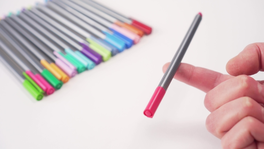 Multi-colored pens on a white table. Hand holds one on a finger in balance. School supplies | Shutterstock HD Video #1049738149