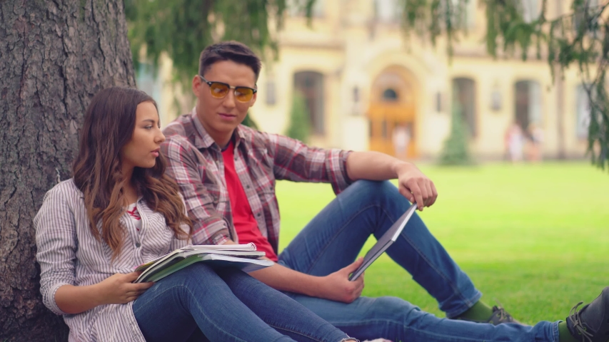 Two best friends or siblings sitting at the campus park and talking leaned on a tree. Brother and sister looking thru notes they made at lecture. Freshmens life. | Shutterstock HD Video #1049974669